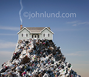 A house sits atop a mountain of garbage with a trail of smoke emerging from it's chimney in a photo about environmental issues.