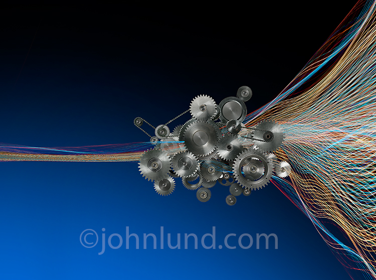 Multi-colored light trails pass through a complex gear assembly in a stock photo about how the Internet works, the Internet infrastructure, and the inner workings of online communications and cloud computing.