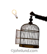 A light bulb ascends away from a bird cage with an open door, held aloft by a business person's hand, in a stock photo about innovation, creativity and ideas taking flight.