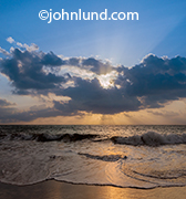 An idyllic tropical beach photo with God rays streaming out from behind a sunset cloud over golden waves gently washing over a sandy beach is a great metaphor for vacations, travel, and getting away from it all.