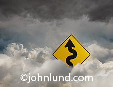 A street sign emerging from the clouds shows a curvy road ahead in