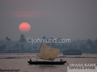 Travel photography - Sail boat at sunset in India with a huge sun dipping down to the horizon.  Behind the boat is a land dotted with palm trees.