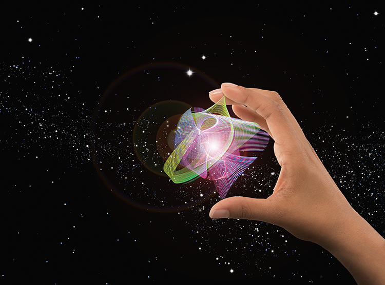 Innovation, research and discovery are all illustrated in this stock photo of a hand holding a cluster of light trails in front of a background of outer space and a star field.