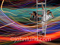 Searching The Internet And Big Data are just two of the concepts illustrated by this stock photo of two people on a ladder with binoculars looking out through a tangle of streaking light trails that represent streaming data, information, and wireless comm