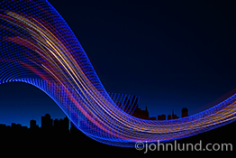 Internet network connections are dramatically illustrated in this photo depicting a tubular network of blue lights containing streaks of color that represent streaming data and wireless and networked communications against a city skyline background.