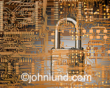 A padlock is embedded in a circuit board in this stock image about Internet security, online protection and the prevention of digital threats and identity theft.