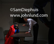 Picture of a superhero being questioned by the cops.  Super hero dressed in a blue costume with a red cape and black gloves. His head is resting in his hands as he sits at the interrogation table. Superhero pic.