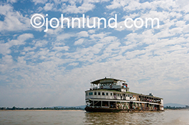 A ferry boat approaches the shore on the Irrawaddy river in Myanmar in this adventure travel stock photo.