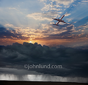 A commercial jetliner flies above storm clouds towards blue sky, better weather, and better times.