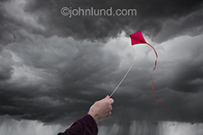 A red kit flies high against the storm clouds in an image about innovation, creativity and ideas.