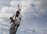 A group of ambitious business people climb over each other on the corporate ladder of success. Picture of a group of people climbing a ladder.