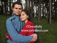 Stock image of a hispanic or Mexican couple hugging in the woods. Deep in the forest this romantic couple is posing for a portrait.  Dense thick stand of trees in the background. Romantic advertising pictures of ethnic people.