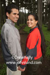 Picture of a couple in the woods.  Stock photo of a happy smiling mexican couple looking back over their shoulders toward the camera.  Romantic photos of hispanic couples for advertising.