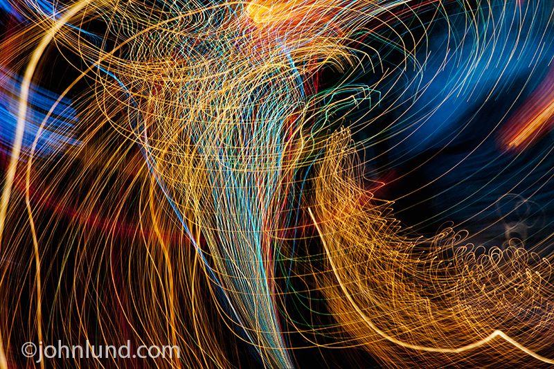 Colorful streaks of light swirl around in a storm of chaotic color, speed and motion in an abstract image about technology and the future.