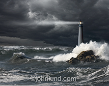 In this stock photo a lighthouse shines it's beam across rough seas as waves batter it and gulls circle overhead.