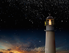 A lighthouse stands against a starry night sky, its keeper standing at the rail as the last of the sunset glow fades away in a beautiful lighthouse picture.