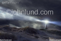Lighthouse storm: A lighthouse casts a beam over a rough sea in a stock picture and fine art image about risk, danger, guidance and salvation.