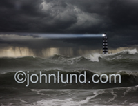 A shaft of light shoots out over the ocean from the lighthouse in this ocean storm. An ocean squall is the background for this lighthouse in a storm photo.