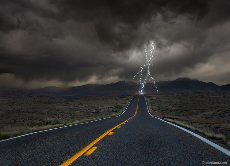 A series of lighting bolts strike the road ahead under stormy skies in this stock photo about the way forward, the future, obstacles and challenge.