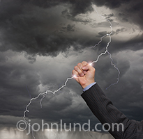 A businessman's hand reaches up and grabs a lightning bolt against a dark, stormy sky in this concept stock photo about opportunity, action, courage and moxie.