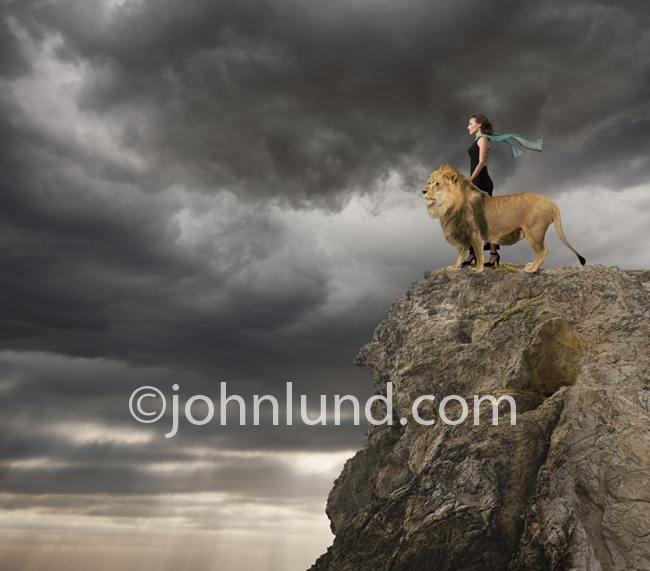 A woman stands next to a Lion and they look out together over the land from atop a cliff.