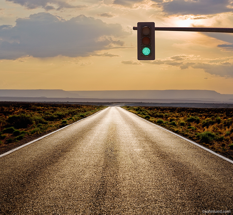 A long straight road stretches in to the distance towards a sunset, and beneath a green stop light in a visual metaphor for opportunity, possibilities and the way forward to the future and success.