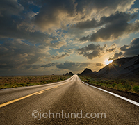 A long, straight road stretches out and over a ridge, lit by the golden light of a sunset, in a stock photo that speaks of journeys, the way forward, freedom and new beginnings.
