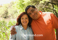 Picture of a middle-aged Mexican couple hugging outdoors. Family outing photos.  Man in orange shirt with his arm around his wife of many years. Old married couple pics. Happy Mexican family photos.