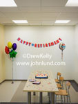 Photo of an empty lunch room or conference room at work and decorated for a retirement party. There are balloons, a banner, confetti and a sheet cake on the table.