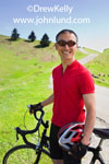 Chinese American or Asian man standing next to and holding his bike up with one hand is smiling at the camera. Pics of fit healthy Asian or Chinese athletes. Scenic rolling grass covered hillside.