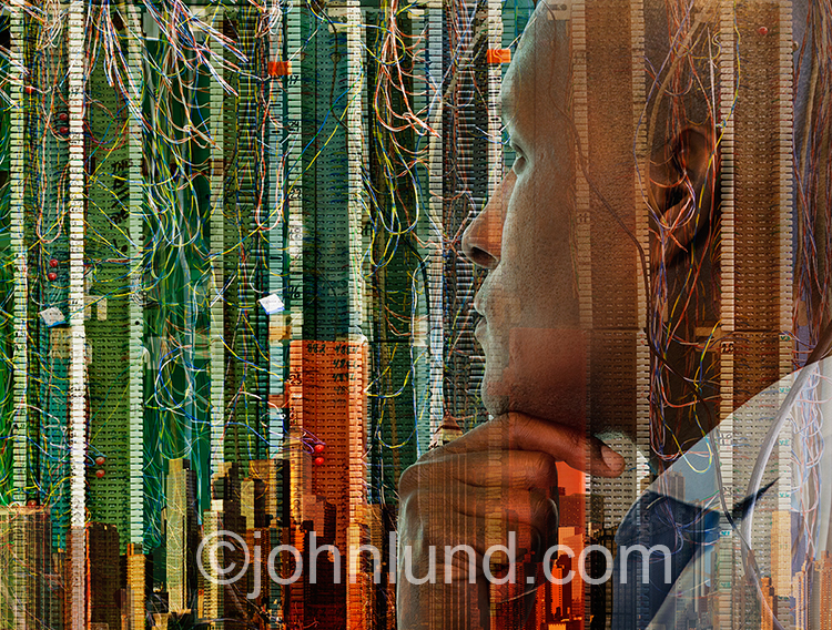 An African American executive businessman contemplates a skyline double exposed with communications technology in a stock photo about technology, communications and the future of business.