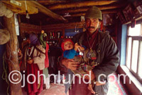 Picture of a man from the Dard tribe of India with a child in his arms. This man's village had recently suffered damage when shelled by insurgents.