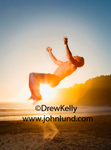 A man is doing back flips at the beach during sunset. The man is above the sand, arms outstretched beginning his flip. The sun is setting over the ocean in the background. Man jumping for joy.