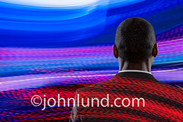 Blue, red and white light trails flow across the frame and enmesh a business man contemplating the future in this stock photo about technology, communications, streaming information, leadership and big data.