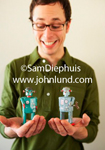Business stock photo of a geeky looking man holding toy wind-up robots in his hand. The man is wearing glasses, is skinny, has on a green shirt, and is smiling at the toy robots in his hands.