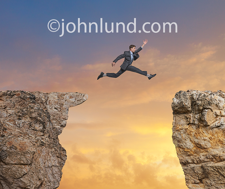 A man makes an takes the leap, an exaggerated leap, from one cliff to another in a humorous stock photo about challenge, courage, risk and possibilities.
