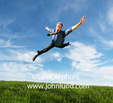 Picture of a businessman leaping into the air with limbs askew.  The man is several feet off the ground with arms and legs all spread out and necktie flying. The ground is covered with lush green grass.