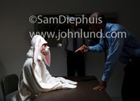Funny picture of a man in a silly looking bunny rabbit costume is being questioned by the police. The rabbit guy is sitting at a table in a darkened room with a couple of cops questioning him. Man in rabbit costume pic.