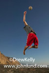 Picture of a man jumping up high to serve a volleyball. The man is playing beach volley ball next to the ocean. Man wearing red shorts against deep blue sky background. Sports play at the beach.