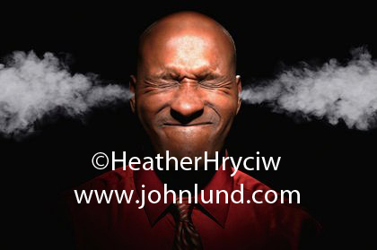 Funny people picture of a black man with smoke billowing out of his ears and he has his eyes squeezed shut. Unique and interesting pictures for advertising.  Bald black man with smoke shooting from his ears. Scrunched up face.