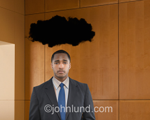 Stock photo of a businessman standing under a black cloud in a corporate environment and showing challenge, disappointment and depression in the business world.