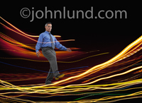 Photo of an Asian businessman walking on a tightrope of streaming data in the form of a glowing flow of light. A picture of communications and connection.