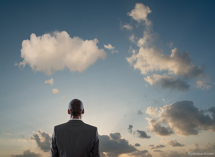 A businessman looks up at a sky in which the clouds form a thought bubble over him in an image about contemplation, decisions and communication.