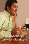 Close up portrait of a handsome rugged looking young adult man having dinner with friends. There are glasses of red wine on the table.  The man is wearing a lime green shirt.  A woman is partially visible behind him.  Wavy black hair and clean shaven.