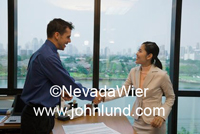 Businessman shaking hands with a businesswoman. The business people  shaking hands are multi-ethnic in this picture. Business people shaking hands in a high rise office building.