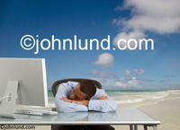 Stock picture of a businessman dreaming of vacation on a warm ocean beach in the tropics. The man dreaming is asleep with his head in his arms on his desk.
