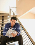 Image of a handsome hispanic man sitting on his stairs at home reading the newspaper or a magazine.
