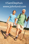 A mature Asian couple is hiking along the Northern California coast line. He has a walking stick and is wearing a light green shirt, hiking shorts, and hiking boots. She has on a light blue blouse, hiking shorts, and hiking boots.