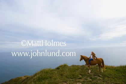 Scenic photo of a woman astride a horse on the edge of a grassy cliff overlooking the pacific ocean. Beautiful shot of a mature women on horseback along the coast. Scenic advertising photography.