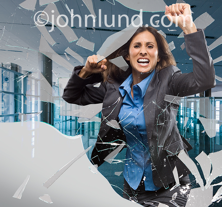 "The ""me too"" movement could use this stock photo of a woman breaking through a glass wall for illustrating the end of silence and the conversion of anger and humiliation to action in gaining truly equal rights for women and attaining parity with men in th"